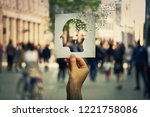 Small photo of Hand holding a paper sheet with human head icon broken into pieces over a crowded street background. Concept of memory loss and dementia disease. Alzheimer's losing brain and memory function.