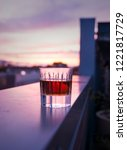 Small photo of A tumbler of whiskey sits on the patio ledge, while a beautiful, vibrant sunrise covers the background.