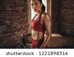 Small photo of Fit and healthy woman standing at gym with skipping rope. Sportswoman resting after workout.