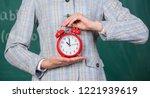 alarm clock in hands of teacher ...   Shutterstock . vector #1221939619