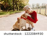 Stock photo pretty young woman in stylish clothes kissing her dog tenderly beautiful blonde with her pet 1222084930