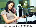 elegant woman looking for dress in clothing store - stock photo