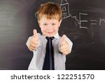 Cute schoolboy against dark blackboard in classroom - stock photo