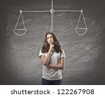 Beautiful brown girl thinking with in the background a blackboard on which is drawn a balance - stock photo