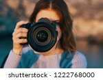 a woman is holding a camera in... | Shutterstock . vector #1222768000