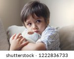 Small photo of Dramatic portrait of little boy sitting on sofa and cuddling teddy bear with scared face,Unhappy Child sitting alone and looking out with worrying face,Toddler boy on corner punishment sitting.