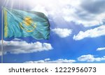Small photo of Flag of Kazakhstan on a flagpole against a blue sky, with a good place for your text.