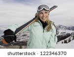 Happy Female Skier With Skis...