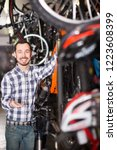 cheerful man in bicycle shop... | Shutterstock . vector #1223608399