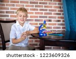 Small photo of Little boy working with microscope for studying microbes. Concept love of science, thirst for knowledge and discovery. Blond hair handsome face, white clean shirt preparing for school. Red bricks wall
