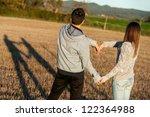 Young couple having fun creating love symbol outdoors. - stock photo