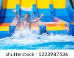 Happy cheerful boy splashing water on water slide at aqua park