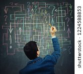 Small photo of Rear view of a young businessman drawing different colorful arrows try to solve a questions maze and find the answer. Problem analysis solution concept.