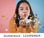 happy asian woman blowing with... | Shutterstock . vector #1224969829