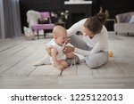 mom changes clothes crying baby ... | Shutterstock . vector #1225122013
