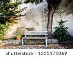 solitary wooden bench under...   Shutterstock . vector #1225171069