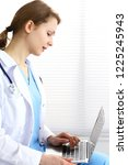 Woman Doctor Typing On Laptop...