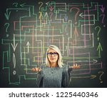 Small photo of Confused young woman in front of blackboard with different colorful arrows try to solve a questions maze and find the answer. Problem analysis solution concept.