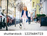 Stock photo a young redhaired caucasian woman walking along european street with small chihuahua breed dog of 1225684723