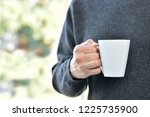 hand of man holding a coffee cup | Shutterstock . vector #1225735900