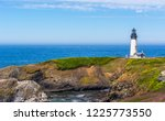 Yaquina Head Lighthouse with meadows, wildflowers, sea cliffs, and the Pacific Ocean photographed on a mostly sunny day in early summer at Yaquina Head Outstanding Natural Area, Newport, Oregon.