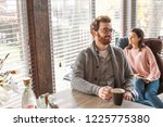 Small photo of Couple of young newly married people settle down in their new rented home, sitting at kitchen, spending time together near big window, with cup of coffee and smartphone
