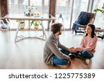 Small photo of Couple of young newly married people settle down in their new rented home, sitting at kitchen, holding hands together and promissing each other never to part