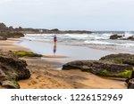 boy walking on a solitary beach ...   Shutterstock . vector #1226152969
