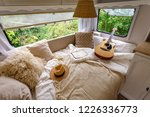 Inside the camper van. Unfilled bed, pillows, guitar, book, hat, white wooden decoration of the house on wheels. - stock photo