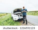 man stand in front of broken car   Shutterstock . vector #1226551123