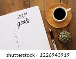 Stock photo top view goals list with notebook cup of coffee over wooden desk 1226943919