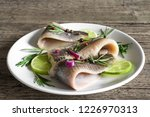 Stock photo fillet of herring with pepper rosemary onion and lime in a plate on rustic wooden background 1226970313