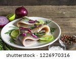 Stock photo marinated herring fillet with pepper rosemary onion and lime in a plate on rustic wooden 1226970316