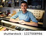 young seller looking at camera... | Shutterstock . vector #1227008986