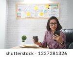 asian woman looking smart phone ...   Shutterstock . vector #1227281326