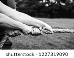 team competing in tug of war | Shutterstock . vector #1227319090