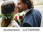 Bride And Groom Kissing Outsid...