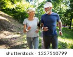 mature couple jogging and... | Shutterstock . vector #1227510799