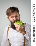 a man with a beard eating a... | Shutterstock . vector #1227574756