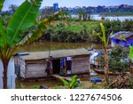 Small photo of Poor floating slumdog village on the bank of Red river, nearby center of Hanoi city.