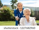 happy nurse and elderly woman... | Shutterstock . vector #1227682960