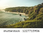 Panorama ocean coastline, green-capped cliff. Indonesia. Spectacular oceanscape the shore surrounded by the grass covered cliffs on the blue sky background. Sumba island, Indonesia.
