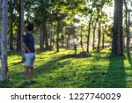 man standing in the forest at... | Shutterstock . vector #1227740029