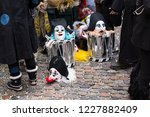 Small photo of Basel carnival 2018. Andreasplatz, Basel, Switzerland - February 19th, 2018. Close-up of a pile of carnival masks and snare drums on confetti covered cobble stones