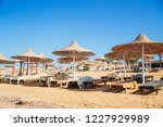 a row of straw umbrellas to... | Shutterstock . vector #1227929989