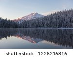 Mount Bachelor reflects over the calm waters of Todd Lake during sunrise in Bend, Oregon.