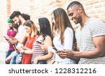 Stock photo multiracial friends group using smartphone at university college break millenial people addicted 1228312216