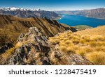 Summer hiking in Isthmus peak Wanaka popular touristic area. Beautiful view from Isthmus peak trail, New Zealand. Scenic panorama view to blue lake, mountains with snow, nice valley and hills around.