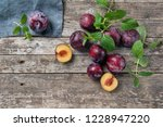 ripe plums on a rustic wooden...   Shutterstock . vector #1228947220