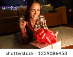 young woman open a gift on... | Shutterstock . vector #1229086453